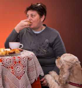 Mother and daughter having tea with apple pie on an orange  background